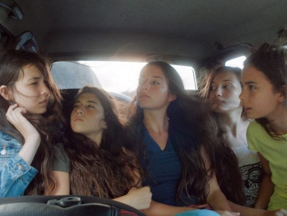 Five young women in the back of a moving car.