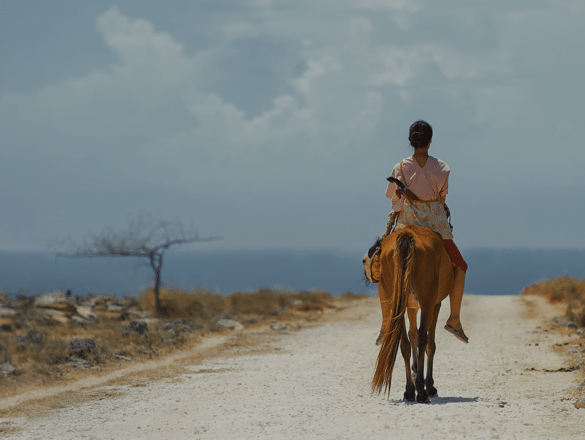 A woman rides off into the distance on a horse, on a dusty road.