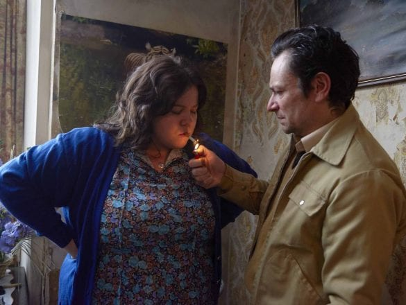 A man lighting a womans cigarette in a house.
