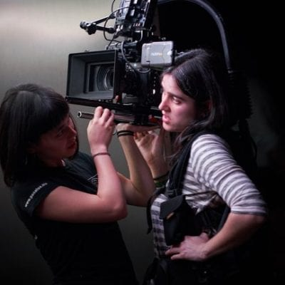 A woman with medium length black hair stands wearing a camera rig with a large digital camera on her right shoulder. An Assistand Camera woman with a navy t-shirt and bobbed brown hair is asisting her by wiping the camera lense.