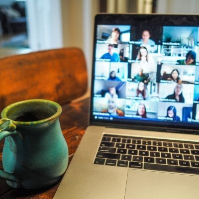 Photo of a table with cup next to a laptop featuring multiple images of people on a webinar