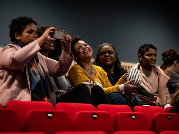 5 women sit smiling and taking photos in a cinema screen