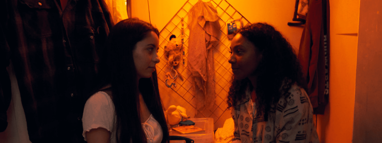 Two late teenage women, one Black with long curly black hair and the other white with long straight black hair, sit looking meaningfully at each other in a warmly lit closet.