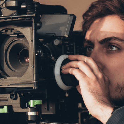 A South Asian man stares intently into a high spec film camera