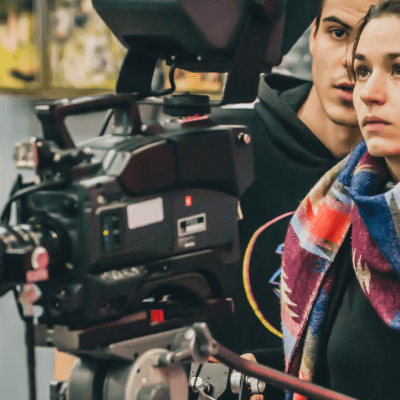 A white woman with a multi-coloured scarf is operating a digital film camera