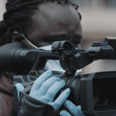 A Black man with a medical face mask is holding a camera with gloes and looking down the view finder