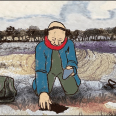 A bald, elderly man with a blue coat and a red scarf kneels in the middle of a field with a metal detector to his left and his green satchel to his right
