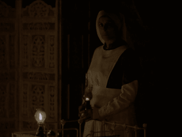 A middle aged woman is wearing an old fashioned marton's uniform stands in a late 19th century hospital ward. The room is dark and she holds a candle which illuminates babies cribs and an white wooden room divider.