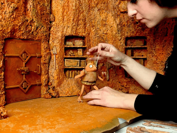 A woman in a black top is painting the eye of a small orange bug like puppet on the stage of a stop motion animation set on Mars. The set includes a small door built into rock and two bookcases.