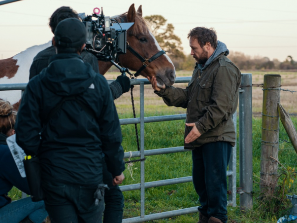 A white man with brown hair in hi forties wearing a green coat tenderly strokes the face of a large brow horse. A camera person and two addtional people from the camera team can be seen with just in front of him with a camera, sound boom and clapper board