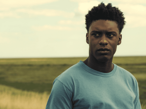 A young Black man with a light blue t-shirt stands in a field looking pensive.