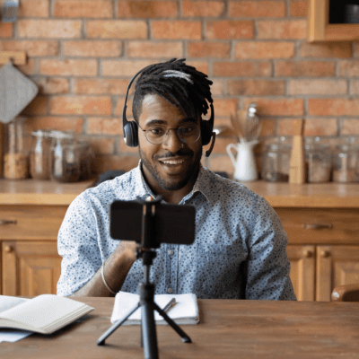 A Black man with glasses wearing a light blue shirt and black headphones sits in front of a phone on a tripod in a kitchen with wooden worktops and an exposed brick wall.