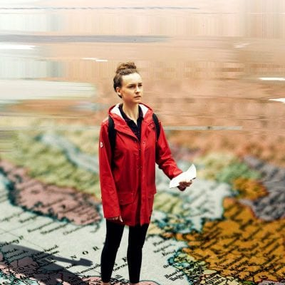 A young, white woman with light brown hair in a bun and a red rain coat satns on what looks like a map of the world while water laps at her feet.